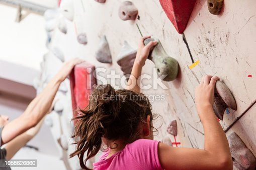 Teenage girl and young man climbing an indoor wall - Extreme Sports