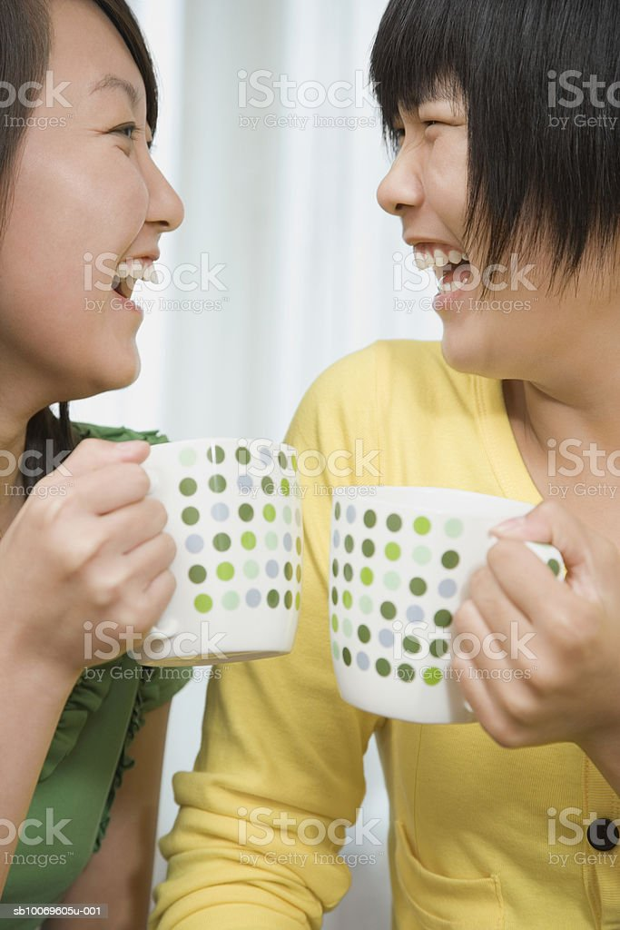 Teenage girl (16-17) and young woman holding coffee mugs, laughing 免版稅 stock photo