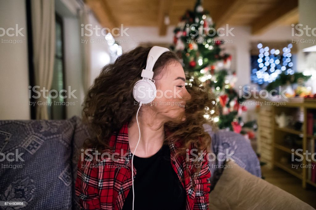 Beautiful teenage girl with curly hair at home at Christmas listening...