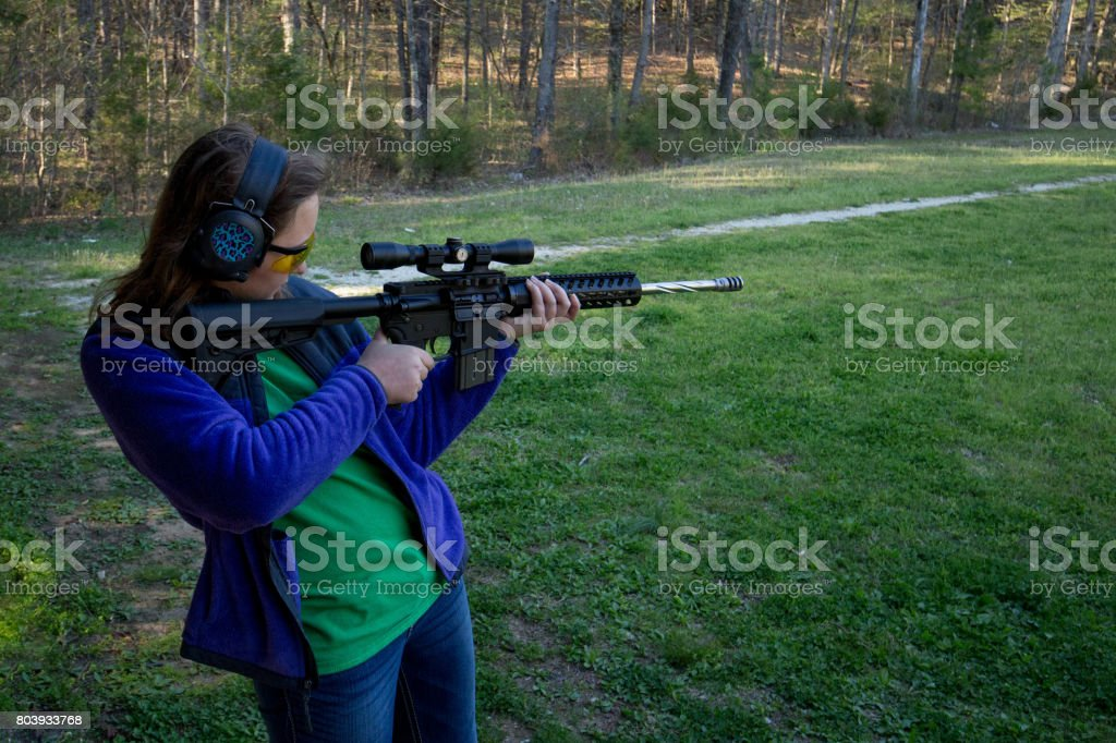 Teenage girl at shooting range stock photo