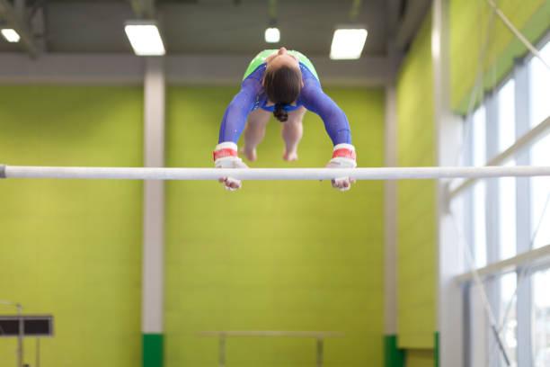 teenage girl athlete exercising on horizontal bar - horizontal bar stock photos and pictures