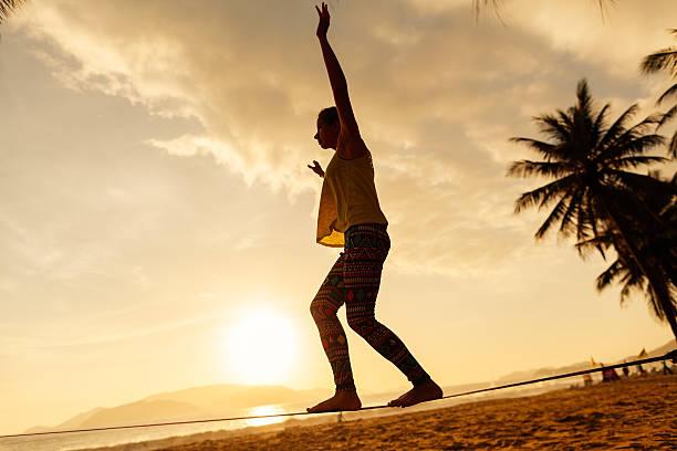Teenager-Mädchen und balancierst auf der slackline silhouette am Strand – Foto