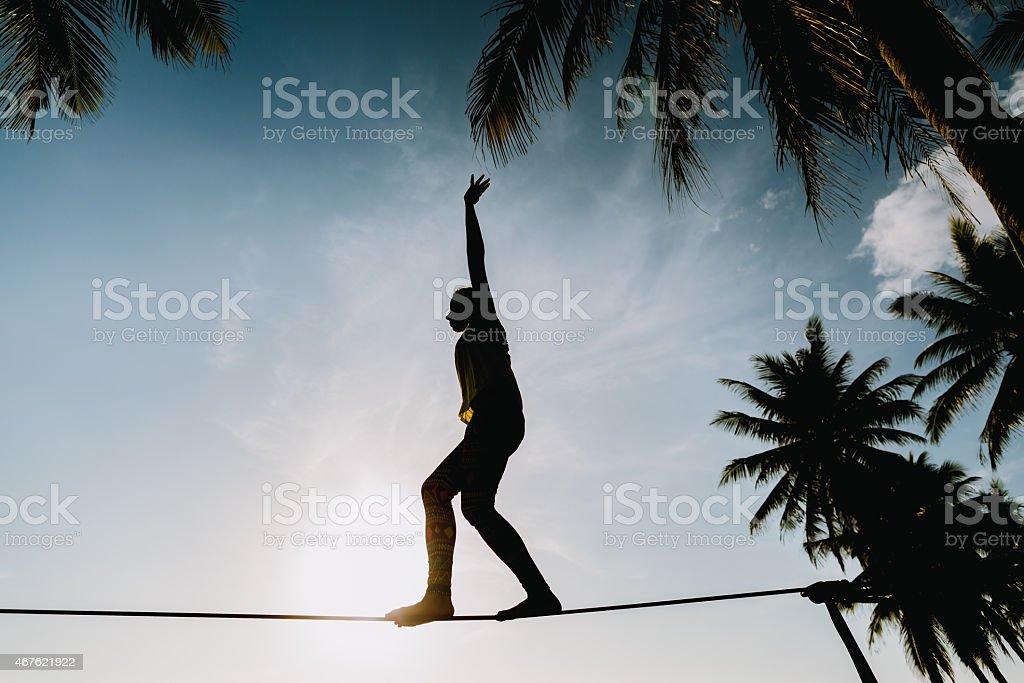 Mädchen und balancierst auf der slackline mit Blick auf den Himmel – Foto