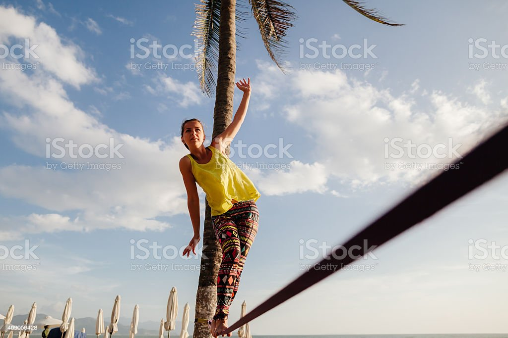 teenage girl  balancing on slackline with sky view stock photo