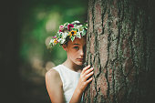 teenage girl behind a tree wearing a floral wreath