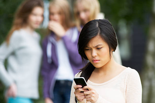 Teenage Girl Being Bullied By Text Message On Mobile Phone stock photo