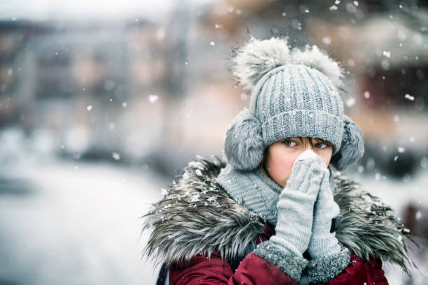 genç kız kış gününde burun üfleme - soğukluk stok fotoğraflar ve resimler