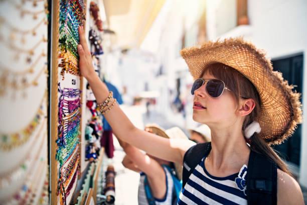 Teenage girl browsing bracelets on street stand in Frigiliana, Andalusia, Spain stock photo