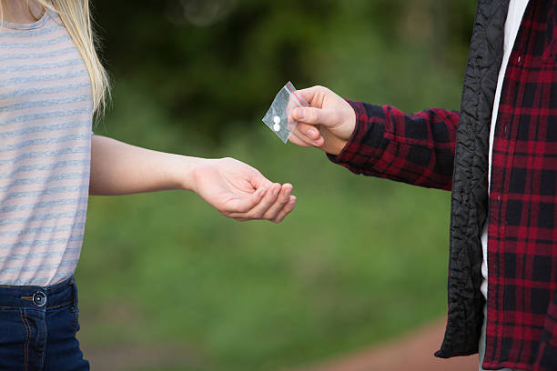 teenage girl buying drugs in playground from dealer - narcotic stock pictures, royalty-free photos & images