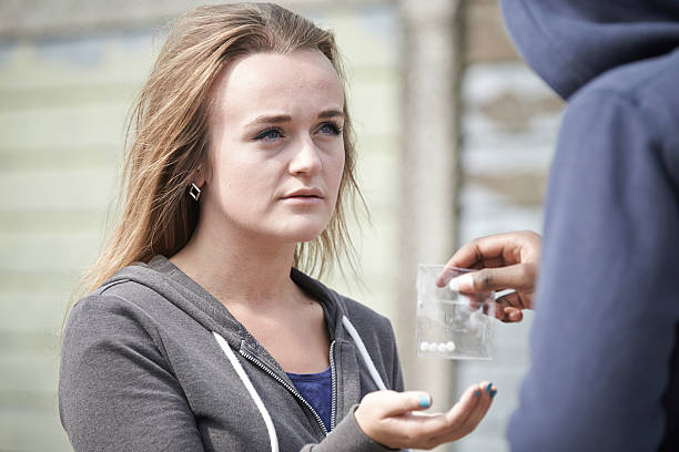 Teenage Girl Buying Drugs On The Street From Dealer Teenage Girl Buying Drugs On The Street From Dealer drug dealer stock pictures, royalty-free photos & images