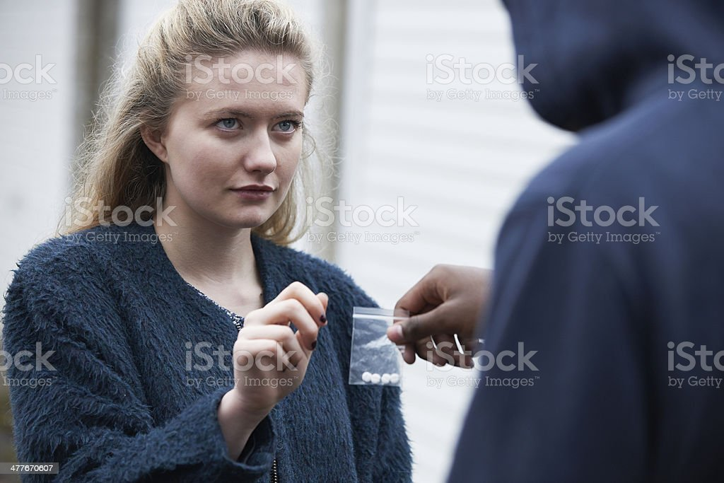 Teenage Girl Buying Drugs On The Street stock photo