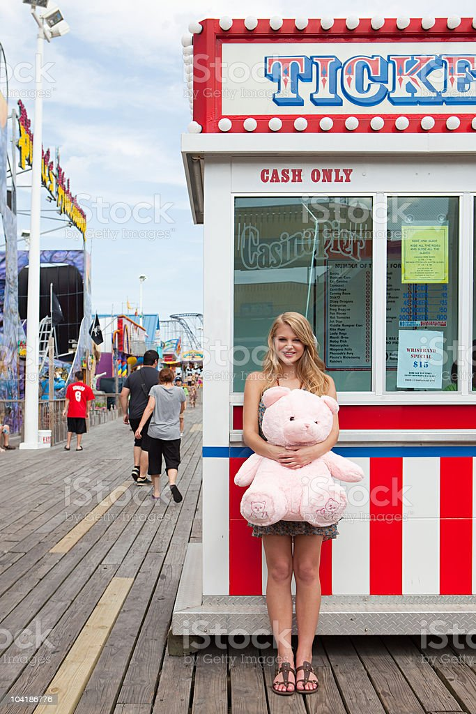 Teenage girl by ticket booth with teddy bear stock photo