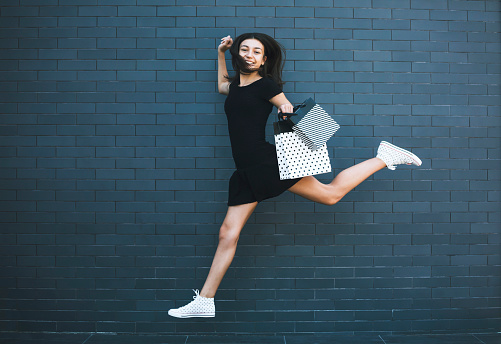 Happy teenage girl carrying shopping bags in front of gray wall. Shopping. Consumerism. Copy space.