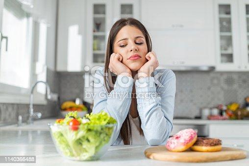 Teenage girl chooses between donuts and vegetable salad