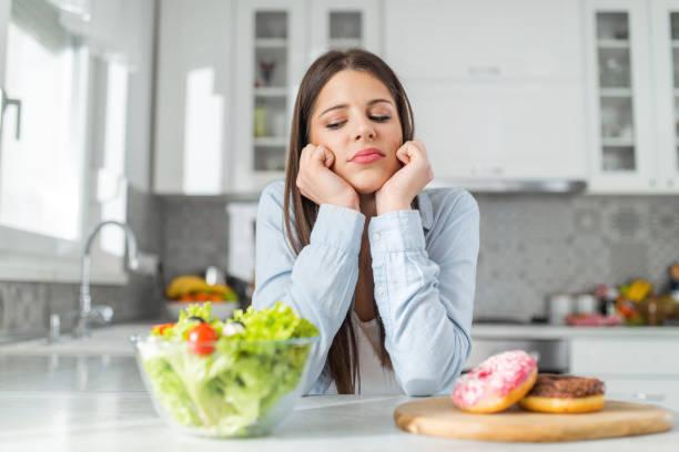 十幾歲的女孩選擇甜甜圈和蔬菜沙拉 - 不健康飲食 個照片及圖片檔