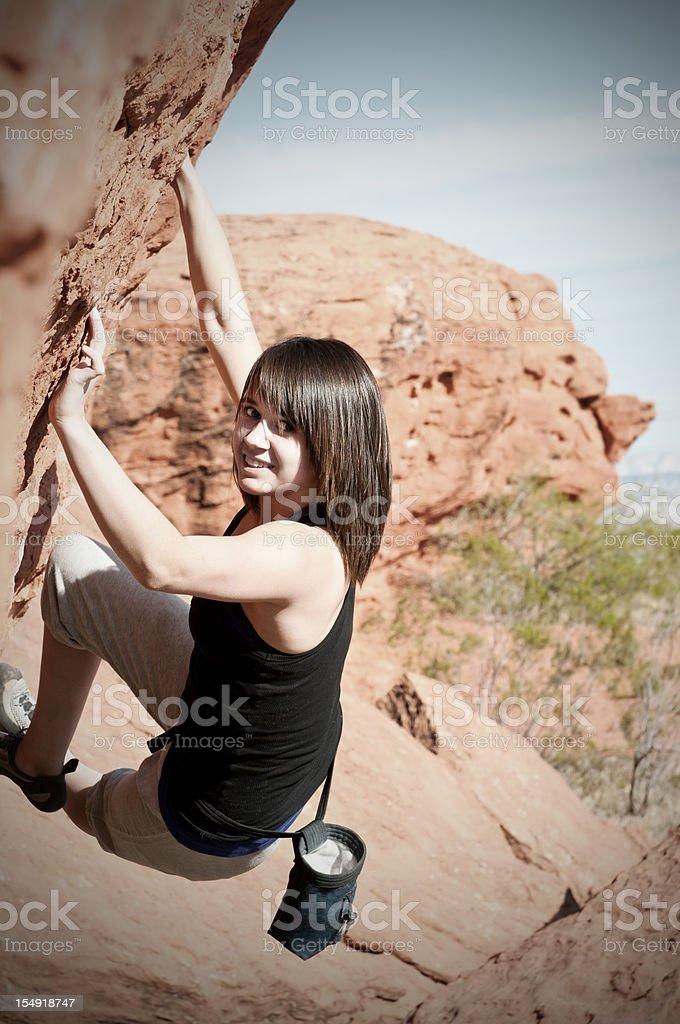Teenage girl climbing boulder in Utah - I stock photo