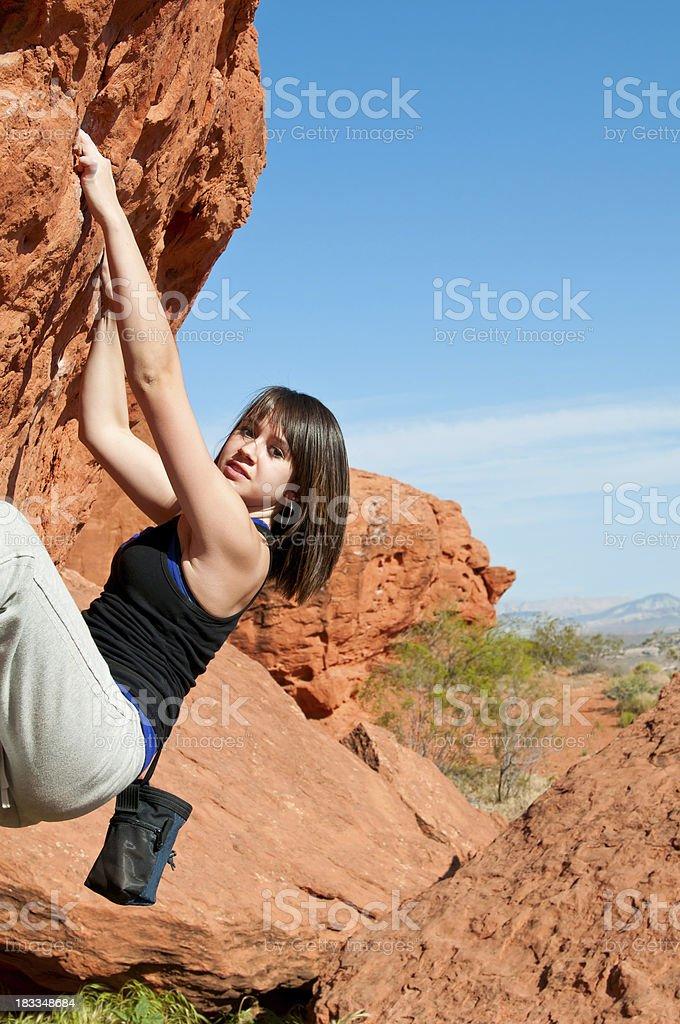 Teenage girl climbing boulder in Utah - II stock photo