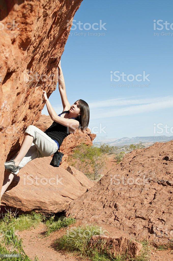 Teenage girl climbing boulder in Utah - IV stock photo