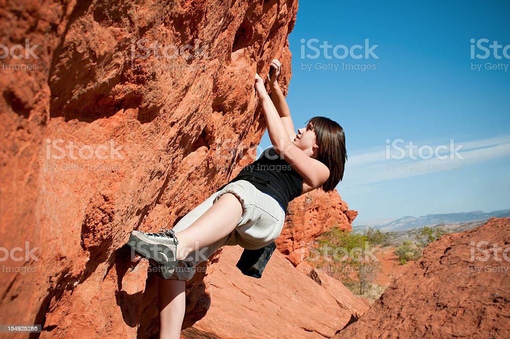 Teenage girl climbing boulder in Utah stock photo