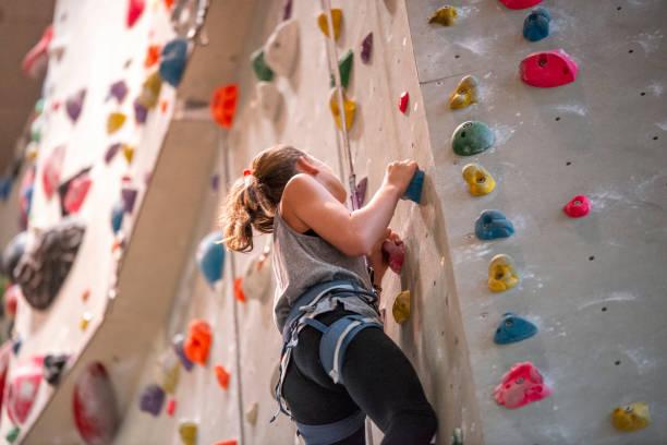 adolescente que escala na parede de escalada - comodidades para lazer - fotografias e filmes do acervo