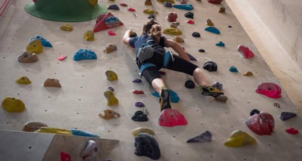 Teenage girl climbing on indoor climbing wall