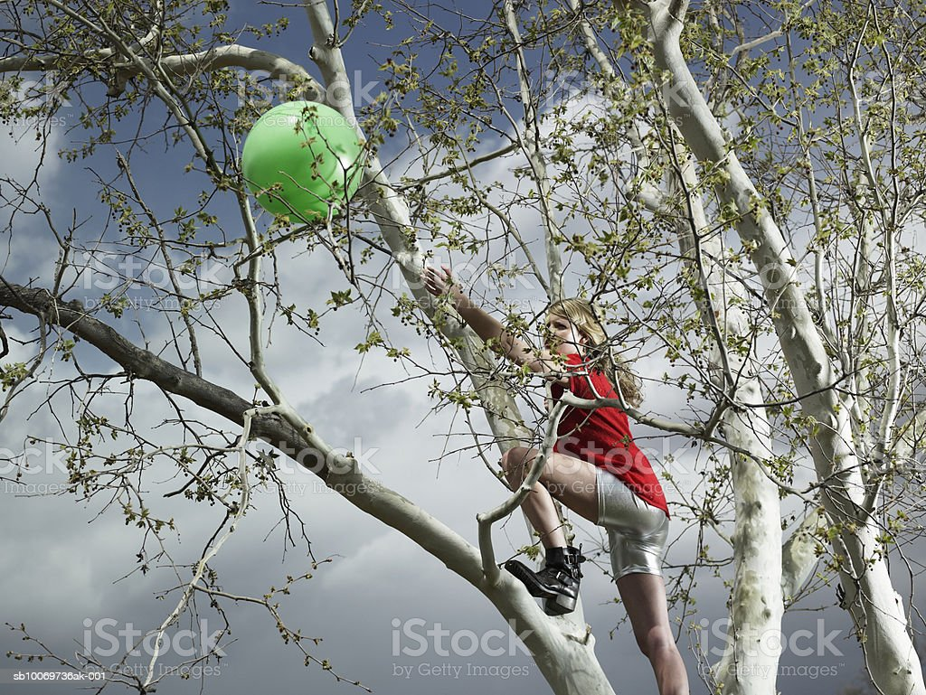 Teenage girl (14-15) climbing tree for ball royalty-free stock photo