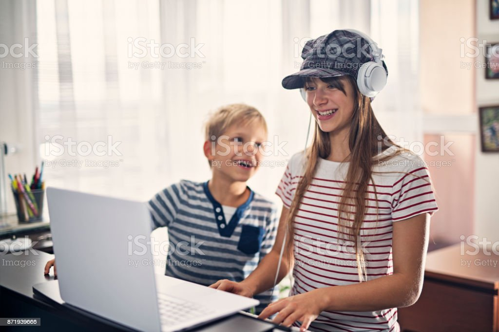 Teenage girl composing music using laptop and electric piano stock photo