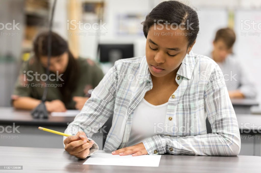 Teenage girl concentrates while taking exam Serious African American teenage girl concentrates while answering a question on a math test. African Ethnicity Stock Photo