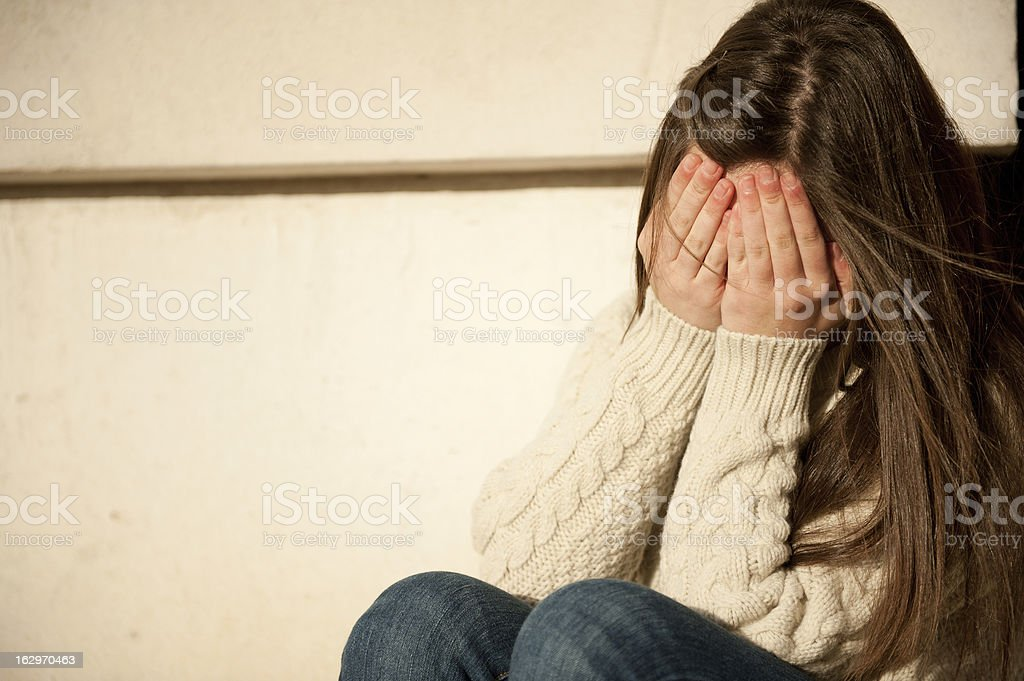 Teenage Girl Covering Face With Hands stock photo