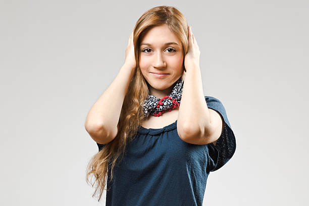 Teenage girl covering her ears Girl covering her ears hands covering ears hear no evil teenage girls women stock pictures, royalty-free photos & images