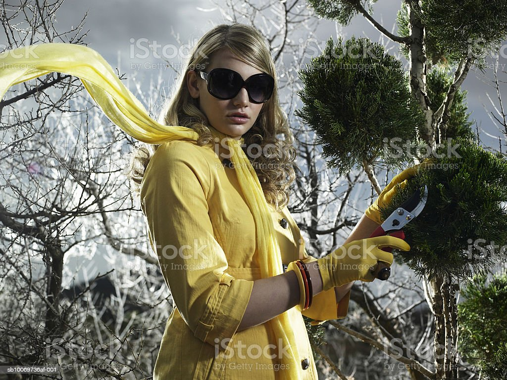 Teenage girl (14-15) cutting leaf with secateurs, portrait, close-up 免版稅 stock photo
