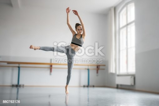young female ballet student training in dance studio