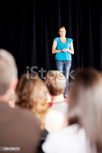 istock Teenage girl delivering a speech on stage for an audience 155428410