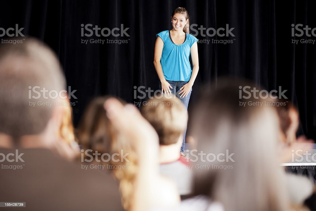 Teenage girl delivering a speech on stage for an audience royalty-free stock photo