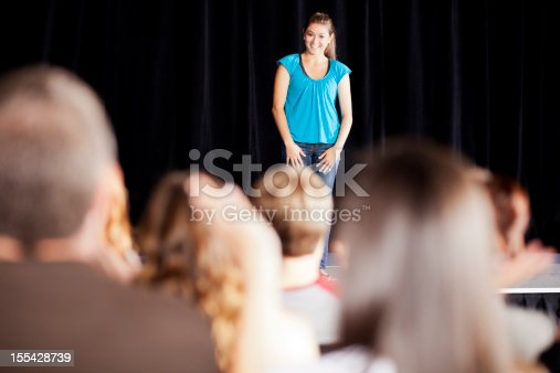 istock Teenage girl delivering a speech on stage for an audience 155428739
