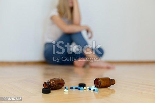 Teenage girl depressed sitting with pills