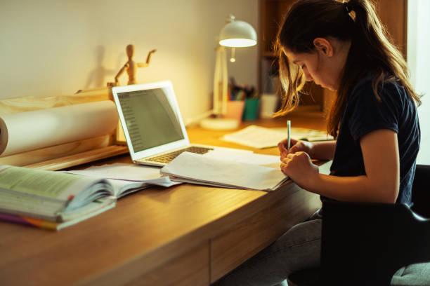 Teenage girl doing homework in her room stock photo