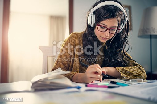 Teenage girl doing homework at home. The girl is listening to the music. Nikon D850
