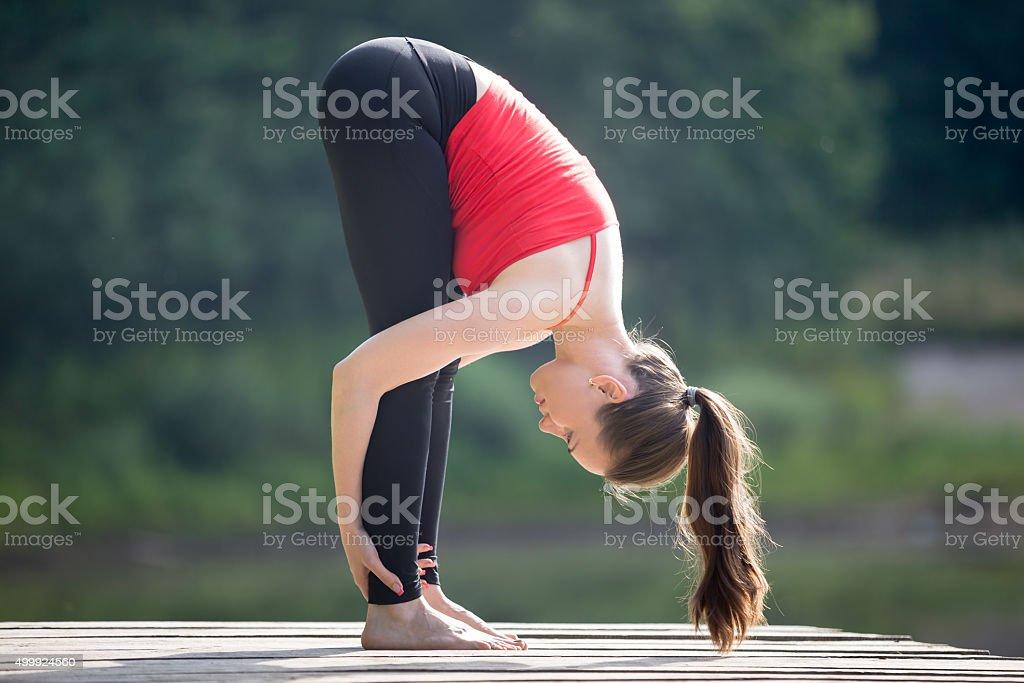 Teenage girl doing Standing Forward Fold Pose stock photo