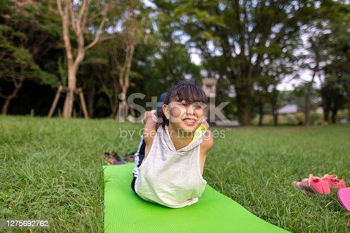 Teenage girl doing yoga on yoga mat in public park - bow pose