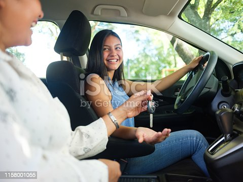 A side view photo of a teenage girl in a car as her mother sits next to her and hands her the keys to drive.