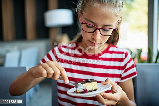 Teenage girl having a piece of cheesecake sprinkled with fruits. Nikon D850