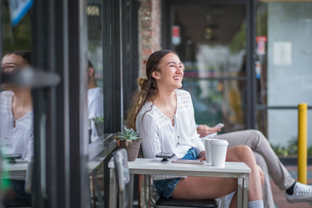 Teenage Girl Enjoying Coffee Outside a Local Coffee Shop Customers sitting at small tables outside a neighborhood coffee shop drinking coffee and text messaging with their cell phones. armenian ethnicity stock pictures, royalty-free photos & images