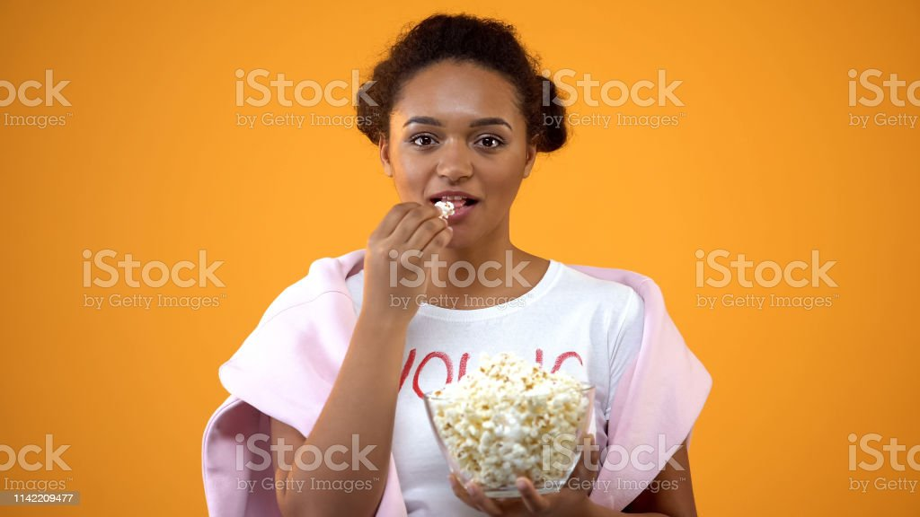 Teenage girl enjoying comedy series on tv eating popcorn on orange...