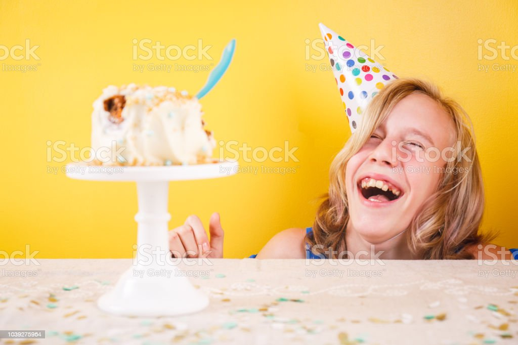 Teenage girl enjoying herself after ruining birthday cake. One person party. Concept of birthday party, messthetics and misconduct. stock photo