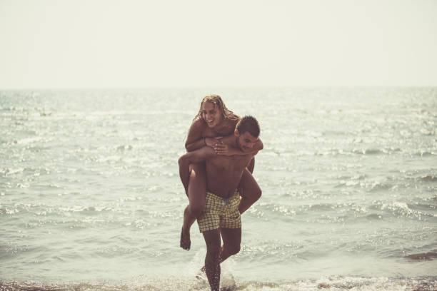 Teenage girl enjoying piggyback ride stock photo
