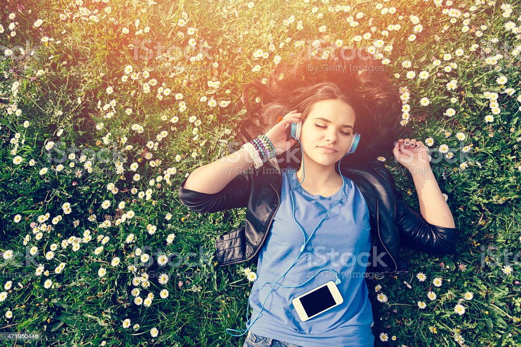 Teenage girl enjoying the music in the park stock photo