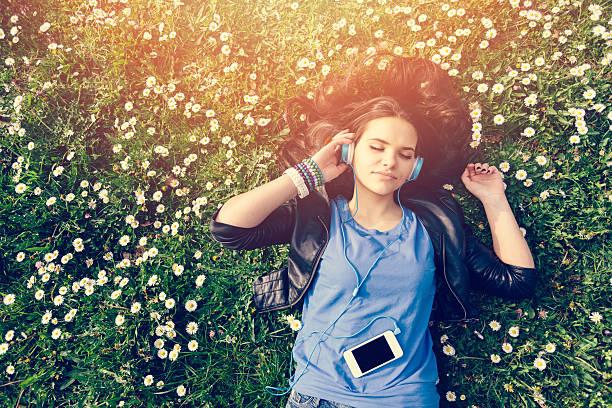teenager-mädchen, die die musik im park - a zone armband stock-fotos und bilder