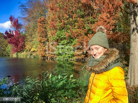 istock Teenage girl enjoying winter at a lake in the middle of a quiet park 1287221871