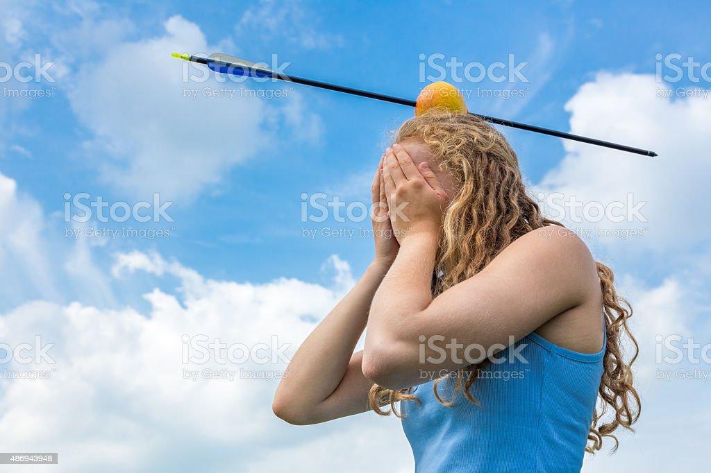 Weiblicher Teenager fühlt sich Angst mit Apfel und Pfeil auf dem Kopf – Foto